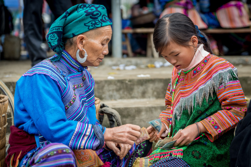 A Blue Hmong woman makes a transaction with a young Flower Hmong woman, in the Bac Ha Market, outside Sapa, Vietnam.