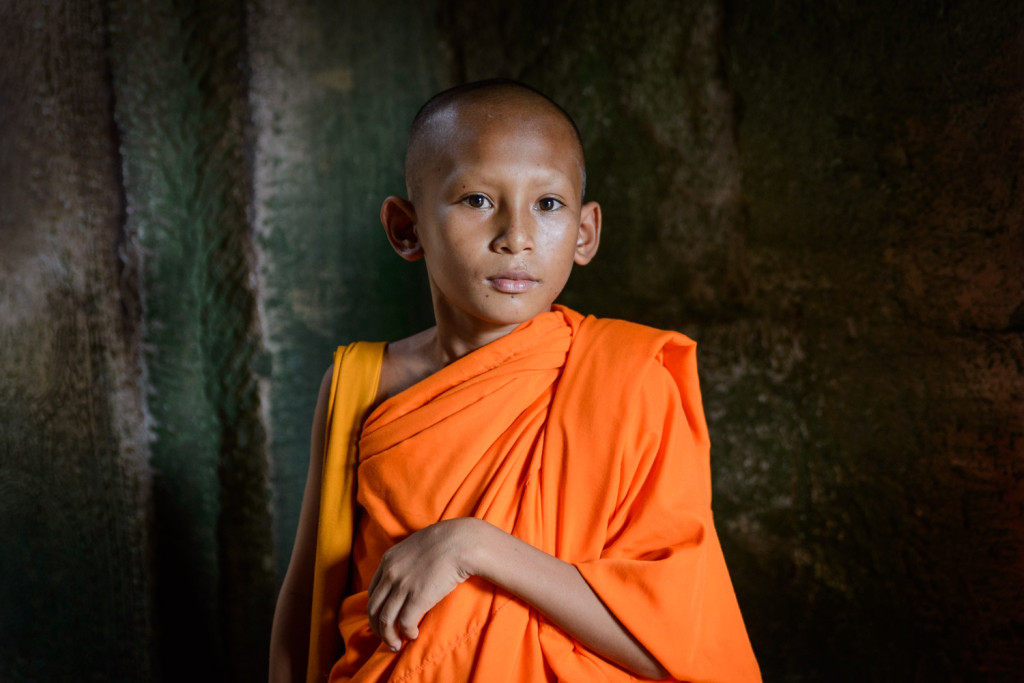 A young Monk inside the Bayon Temple, in Angkor, Cambodia.