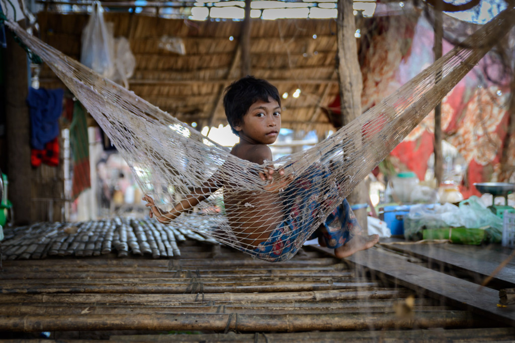 A young boy sits on his hammock underneath his home in Kompong Phluk, outside Siem Reap, Cambodia.