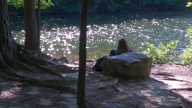 picture of a girl reading her Bible by the water
