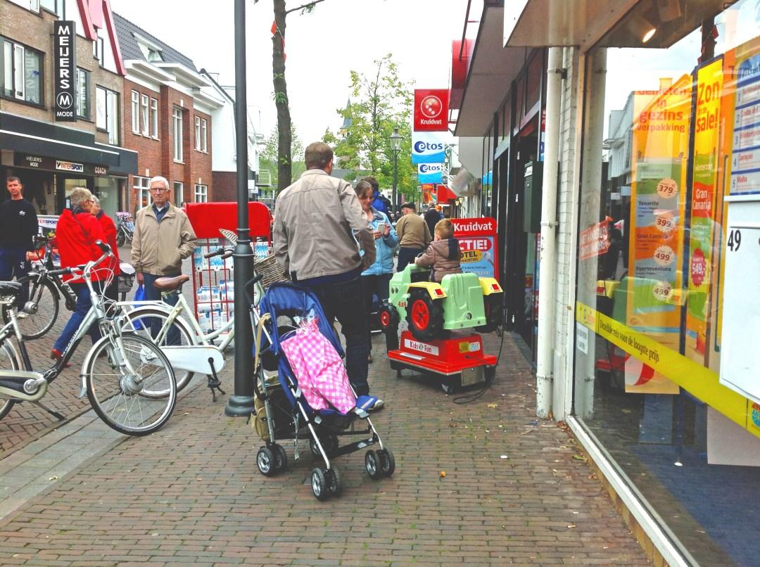 Afbeelding van de Dorpsstraat met geleidelijn en mensen die lopen te winkelen en een geparkeerde fiets welke de geleidelijn blokkeert.