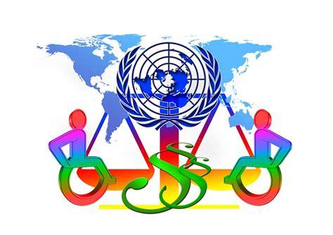 Afbeelding van drie rolstoelgebruikers wijzend naar een wereldkaart