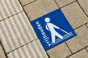 Afbeelding van een campagne sticker naast een geleidelijn voor mensen met een visuele beperking.