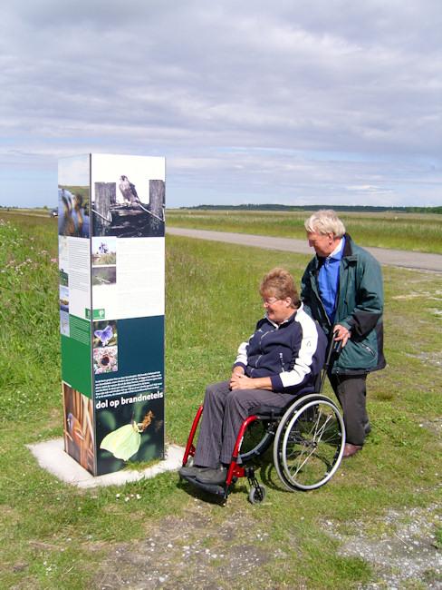 Afbeelding van een vrouw in een rolstoel die door een man door de natuur gereden wordt.