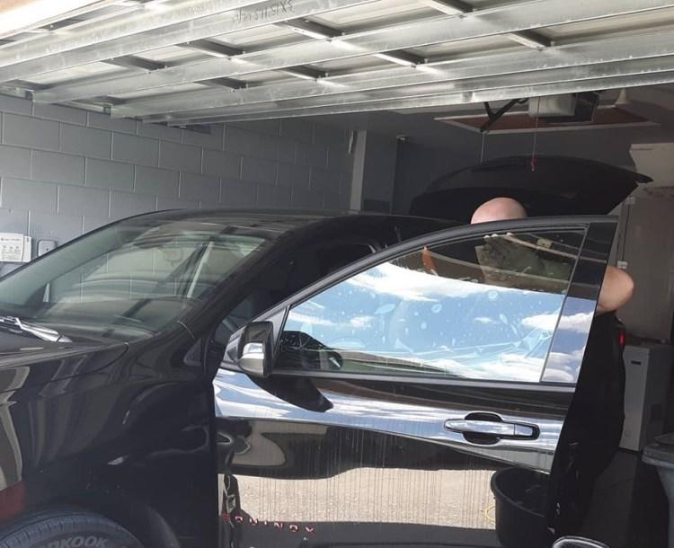 Oviedo, Florida installing window film in a garage. Professional Window Tinting of Central FL LLC
