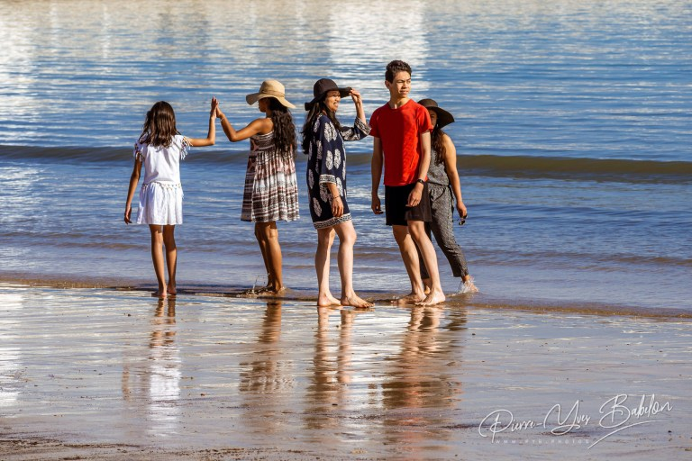 A group of tourists walking on the beach