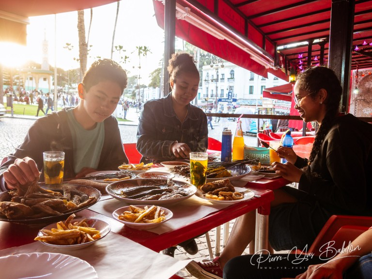 Young tourists eating grilled food