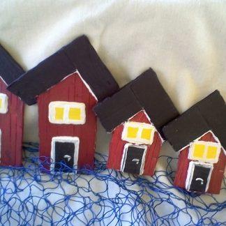Fyra rödsvarta sjöbodar med liggande fönster