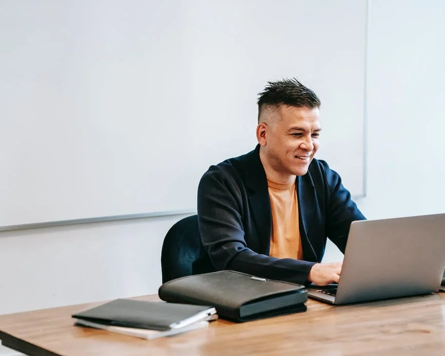 photo of man smiling in front of his laptop