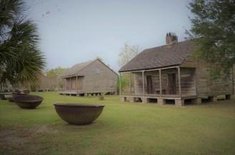 Des cabines d'esclaves avec, en premier plan, une marmite dans laquelle on cuisait les canes à sucre