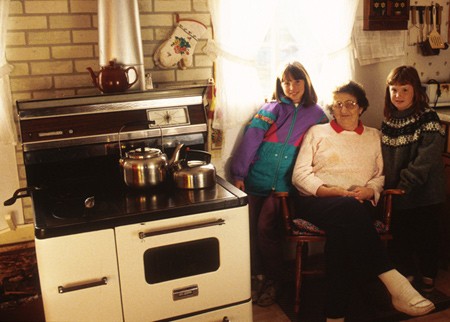 Gladys McGrath with two of her grandchildren in her kitchen in Tilting