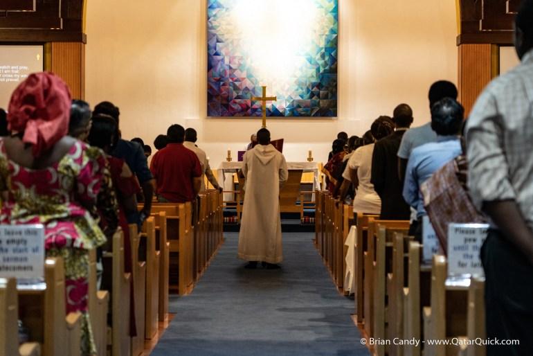 Priest walking down church isle holding cross
