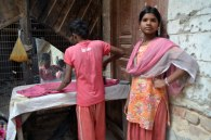 A child labourer irons clothes while his sister stands besides him