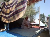 Hajira, 55, sits in a makeshift tent outside her colony, Batamaloo. She says that she was terrified as the sky started to roar. There were Chinar trees around, one of which fell on a mosque and damaged it
