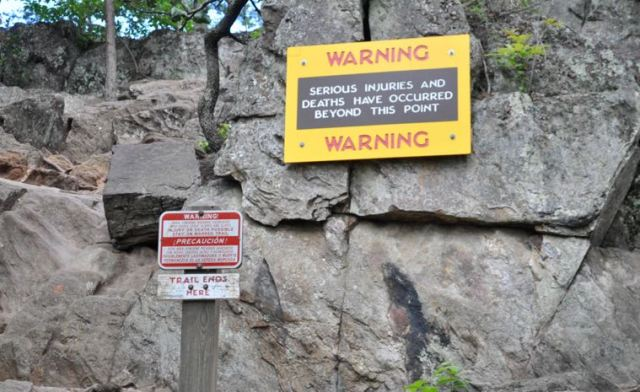 Signs warn hikers of the very real dangers when traversing the rocky cliff of The Pinnacle.