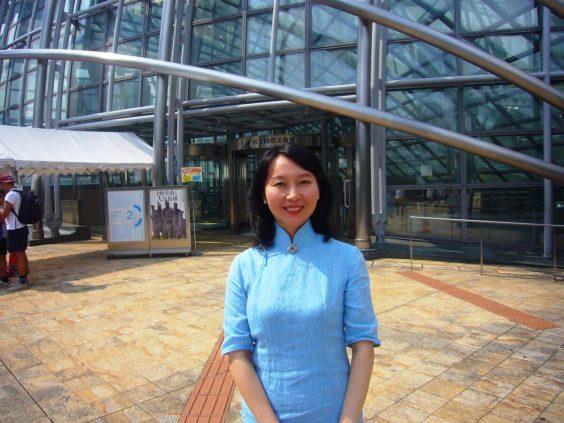 大阪国立国際美術館の前で、チャイナドレスを着たレイレイが笑っている写真。