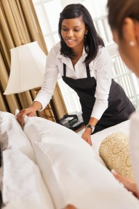 Cleaning crew making bed in hotel room