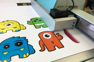 Little cartoon monsters being printed on a flatbed printer
