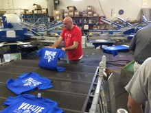 Daniel putting the finished shirts on the drying belt.