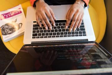 Chica escribiendo código en computadora