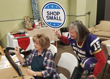 """Artist Sonya Gordon, decked out in UNA football gear, """"coaches"""" student Kathy Shafer during a painting class at High Cotton Arts. Those who take art classes and shop at High Cotton Arts are supporting several small business owners who have studios and exhibit space at the Downtown Athens facility."""