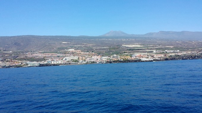 A photo from off the coast of Tenerife. The mountain is in the background with a town in the foreground on the coast.