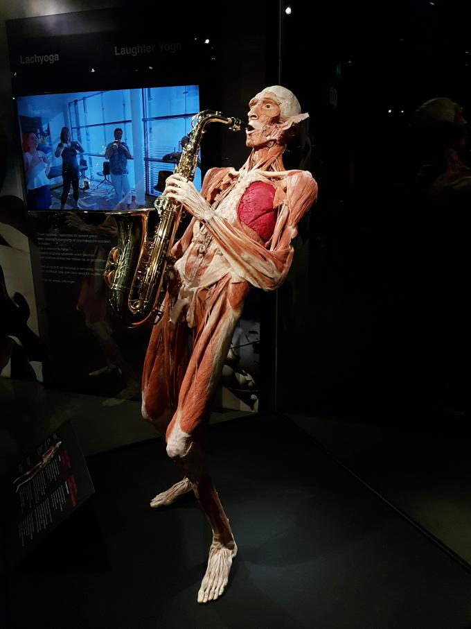 A statue of a man without skin and fat playing a saxophone
