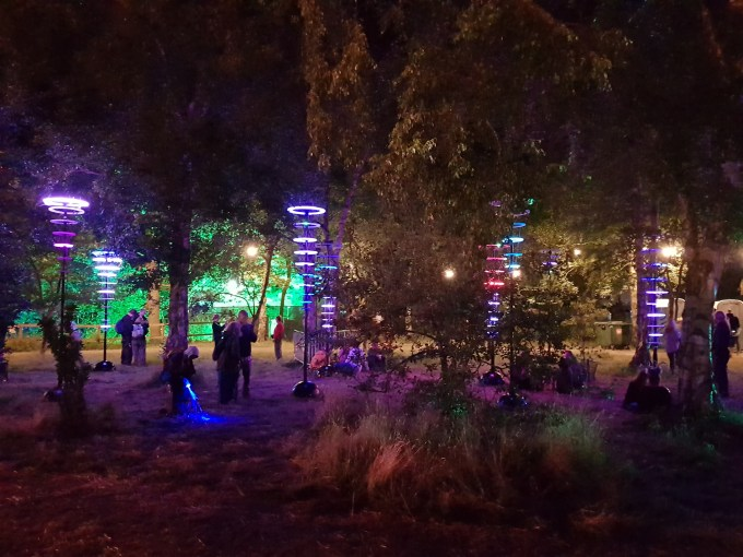 An art installation consisting of a number of vertical poles each with a number of illuminated rings running down them. Trees surround the poles.