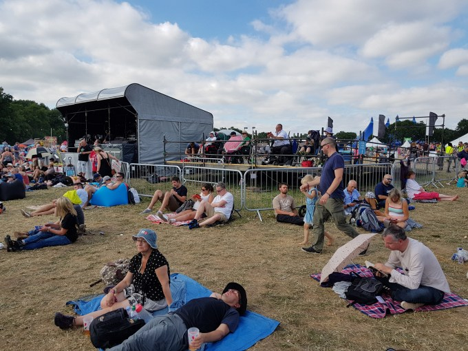 A number of people sat or lying blankets on top of the brown grass. The accessible viewing platform is behind them enclosed by metal barriers.