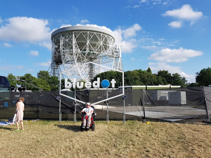 """A young man in a Powerchair sitting in front of a sign that says """"bluedot"""" with the huge Lovell radio telescope dish in the background."""