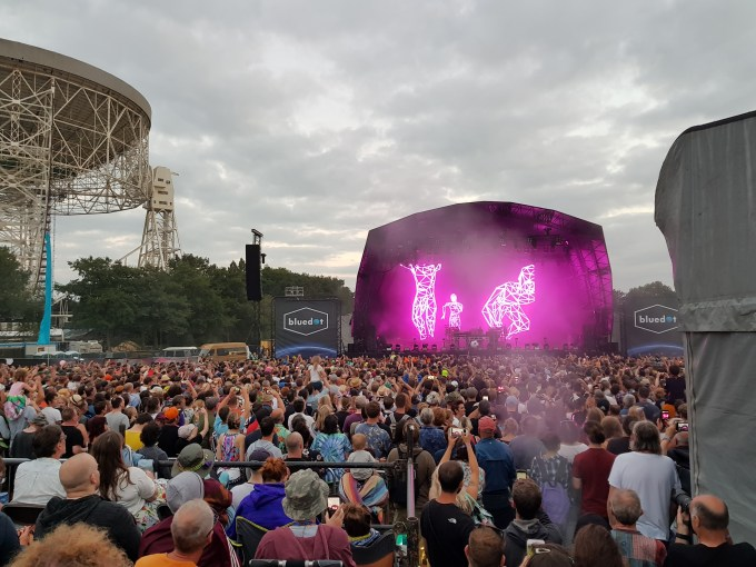 A large crowd is standing in front of a stage watching the chemical Brothers perform.