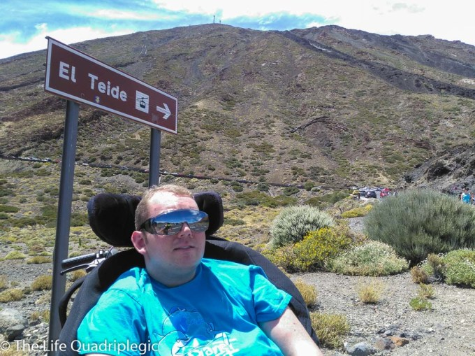 "A male wheelchair user smiles at the camera with a sign pointing to the mountain in the background which reads ""El Teide"""