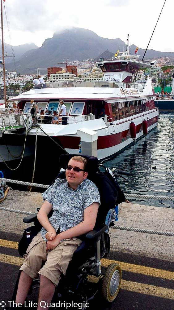 A male wheelchair Use that is that on the edge of the harbour next to the water with a large boat in the background