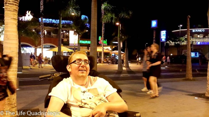 A male wheelchair users miles at the camera at night time with a street behind him and people walking by