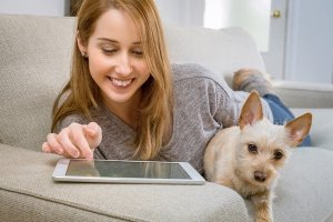 タブレット見る女性と犬