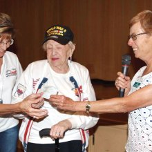 Honor Flight coordinator Kathy Mansur and WWII Veteran Helen Glass receive $1000 check from TWOQC President Peggy McGee.