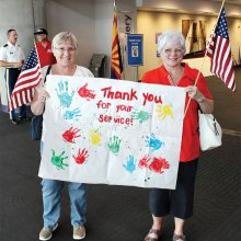 Shelia Parks (left) and Karen Woodrow hold up a banner thanking World War II veterans for their service. The banner was made by Sheila and Drew Parks' four year old granddaughter's Montessori preschool class in Lake Forest, California; photo by John McGee.