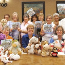 Baby shower committee with donated stuffed animals and children's books donated by Quail Creek Canadian winter visitors; books were written by Yasmin Thorpe, a TWOQC member.