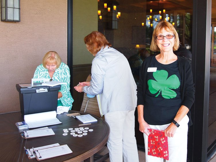 With a big green shamrock on her shirt, Ginny McGinnis gives out the hole assignment numbers to the Lady Putters; photo by Sylvia Butler.
