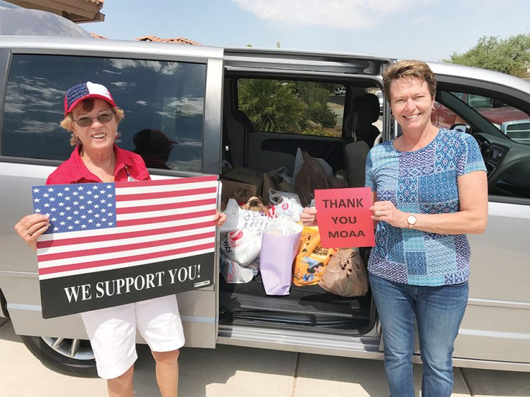 Left to right: Peggy McGee, organizer of the drive, and Barbara Gavre, Family Readiness Program Manager for the Tucson Air National Guard, survey the bags and boxes of donated groceries; photo by Sam Zurcher