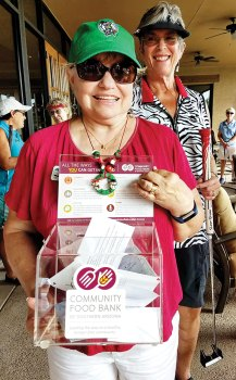 Suzan Bryceland holds the container with $565 to help the Food Bank; photo by Peggy McGee