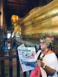 While visiting the Temple of the Reclining Buddha in Bangkok, Joyce Smerick also relaxed reading her copy of the Crossing.