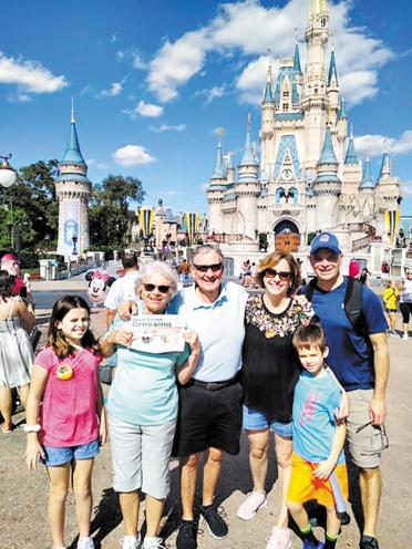 Judy and Paul White along with their fabulous grandkids taking in the Magic Kingdom while reading the Crossing.