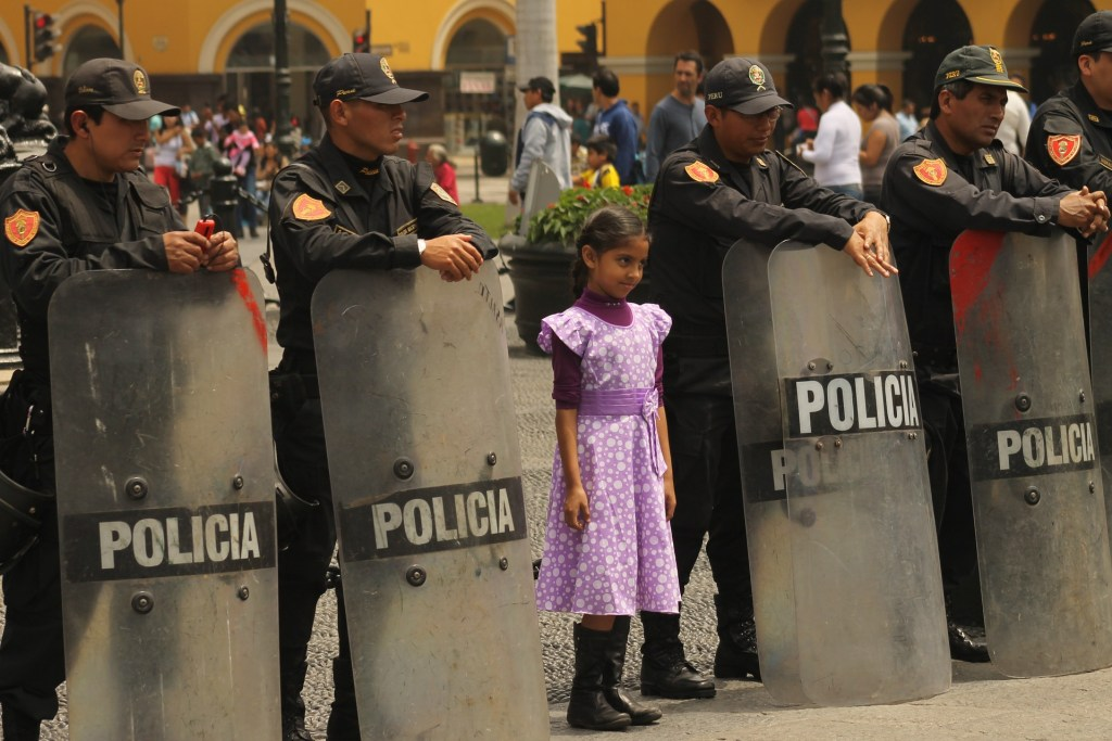 """<img src=""""policelima.jpg"""" alt=""""a row of anti-riot police with a little girl among them"""">"""