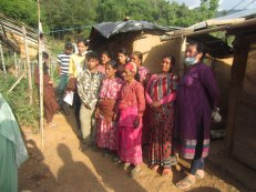 Locals pose for a picture in front of their damaged homes