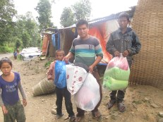 Camp coordinator Bam Bahadur Tamang receives some used clothes for camp residents sent by friends from Kathmandu.