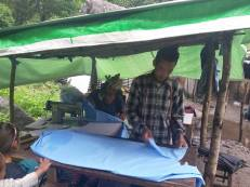 Village tailor making school uniform for the kids