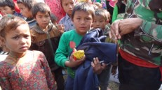 Boy from Satbise IDP camp receives clothes and snacks