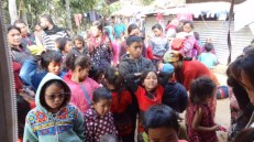 Children from Naubise IDP camp line up for clothes