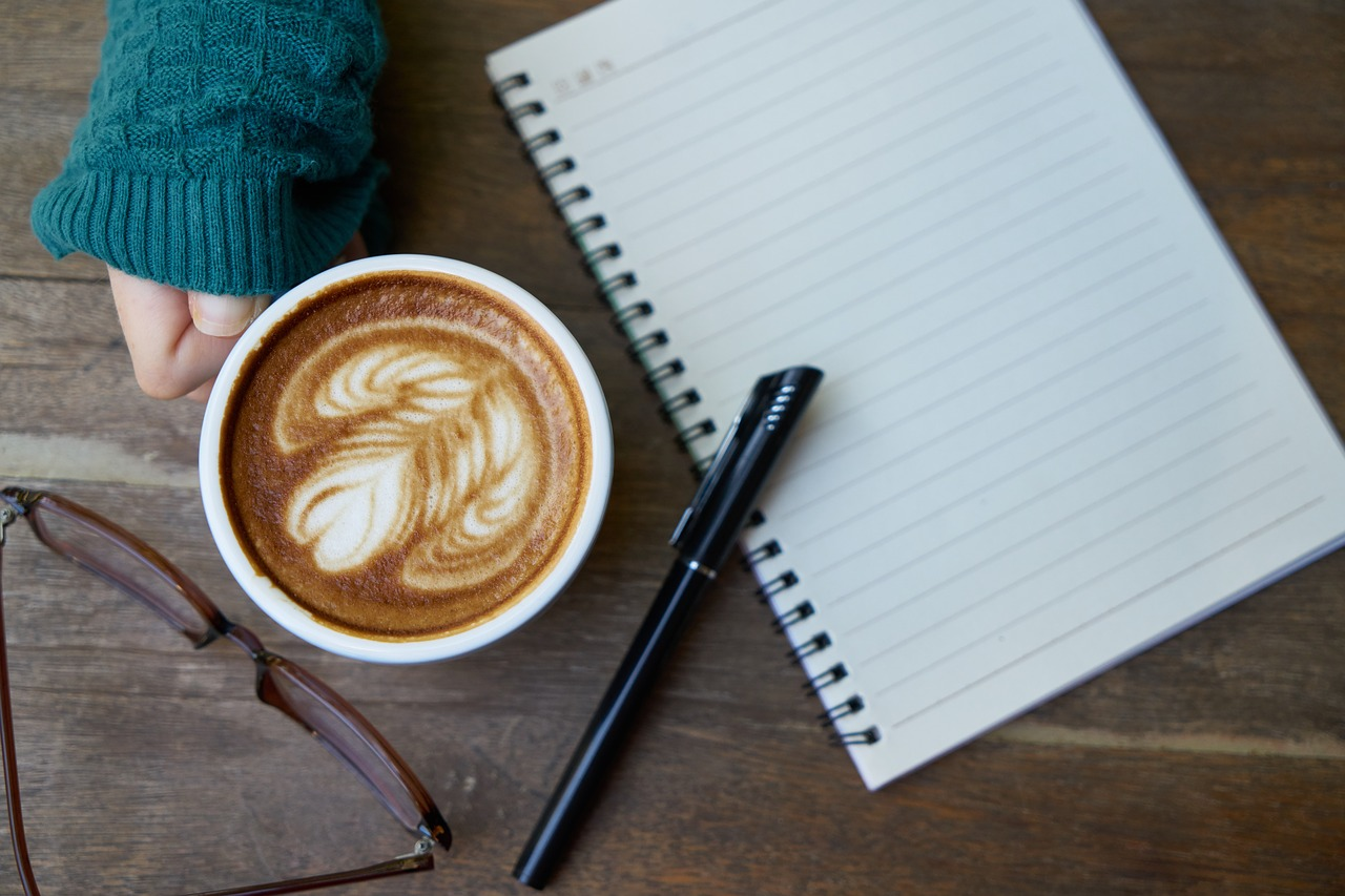 Cup of coffee, pen, and spiral notebook.